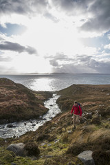 Backpacker hiking along creek on coastline, Torridon, Scotland, UK