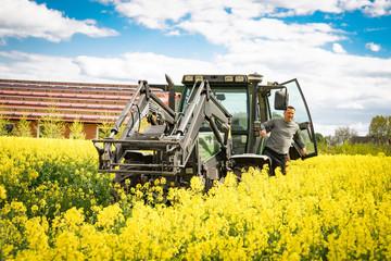 Landwirt mit Traktor in seinem blühenden Rapsfeld