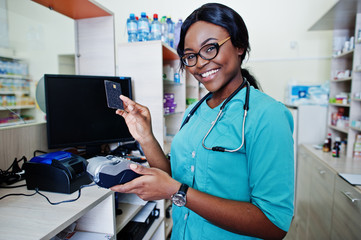 African american pharmacist working in drugstore at hospital pharmacy. African healthcare. Work with payment terminal and credit card.