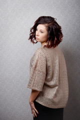 A brown-haired woman in a fashionable sweater and with a stylish hairstyle in profile poses against the gray vintage wall.