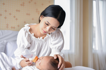 Newborn Concept. Mom is breastfeeding in the bedroom.
