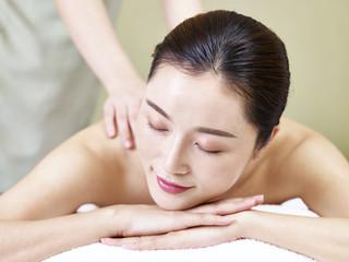 beautiful young asian woman receiving massage in spa salon
