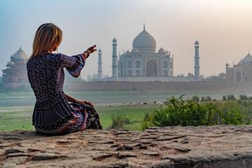 Beautiful girl points to Taj Mahal. Travel concept Wall mural