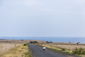 A man skateboards down the road towards Ka Lae, also known as South Point, the southernmost point of the Big Island of Hawaii