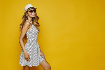 Cheerful and smiling blonde model sexy girl with perfect body, in white striped fitting dress, hat and sunglasses, posing sideways, isolated at yellow background