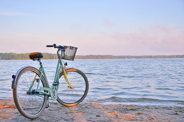 Vintage bicycle with a basket near the lake during beautiful summer sunset. Copy space.