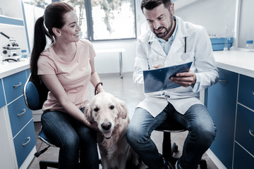 Professional vet. Nice cheerful positive woman smiling and stroking her dog while looking at the doctor