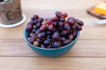 Bowl of red grapes on picnic table