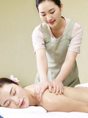 young asian masseur performing massage on woman