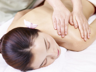 young asian woman receiving massage in spa salon