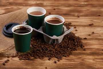Close-up of three take away green paper cups in coffee holder container with coffee beans and hot chocolate drink on rustic wooden table background, top view,