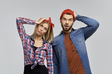funny young couple of hipsters in casual clothes and with hats holding hands behind their heads