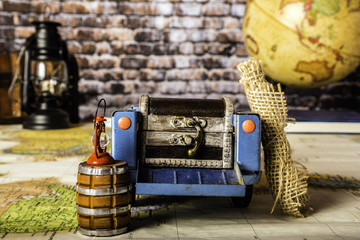 toy car sitting on world map packed for trip with globe and antique lantern with brick wall background