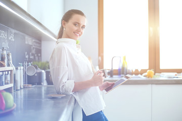 Portrait of young woman standing against kitchen background.