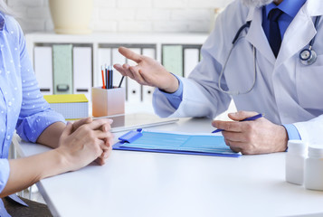 Mature doctor consulting patient in clinic