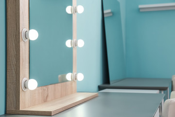 Makeup mirror with light bulbs on table in dressing room
