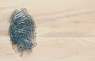 small pile of silver paper clips on a wooden desk with copy space