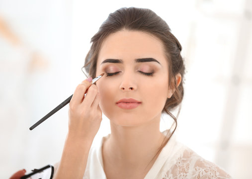 Professional makeup artist working with young woman in salon