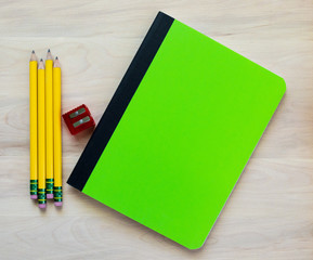 Back to school-4 yellow pencils, a red pencil sharpener and a green notebook with blank cover for customized message, all on a wooden desk