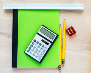 back to school-2 yellow pencils, a red pencil sharpener, a calculator, a green notebook and a triangular ruler on a wooden desk