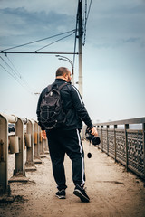 Male photographer traveler with backpack and camera in hand walking on city bridge, view from back, perspective, toned