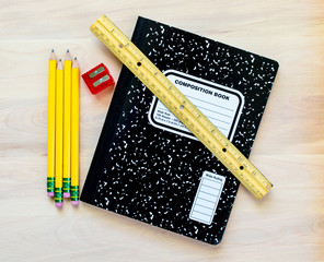 back to school-4 yellow pencils, a red pencil sharpener, a 12 inch ruler ,and a black and white composition notebook on a wooden desk