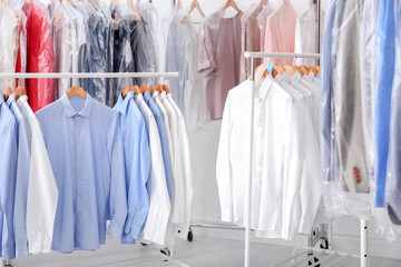 Racks with clean clothes on hangers after dry-cleaning indoors
