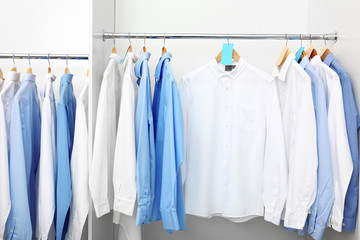Racks with clean clothes after dry-cleaning on hangers in wardrobe
