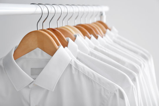 Rack with clean clothes on hangers after dry-cleaning