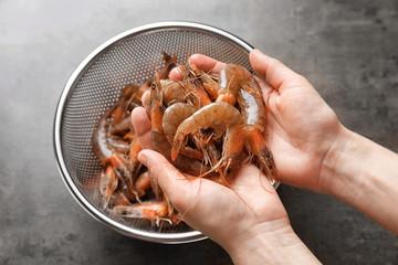 Woman holding fresh shrimps over colander, closeup
