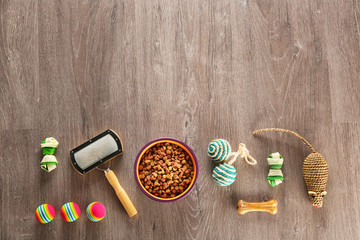 Flat lay composition with cat accessories and food on wooden background