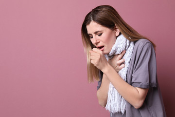Woman coughing on color background