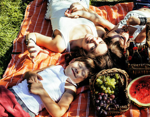 cute happy family on picnic laying on green grass mother and kids, warm summer