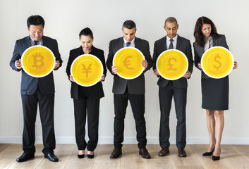Business people standing and holding currency icons