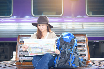 A young Asian woman is looking at travel map while is in the train station.