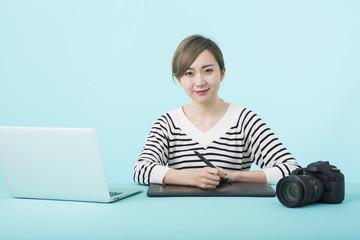 ノートパソコンとペンタブレットで仕事をする若い女性