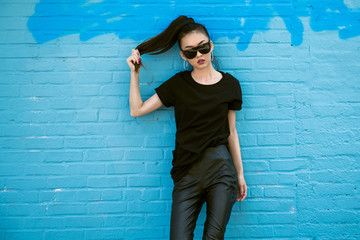 Beautiful fashionable asian girl wearing sunglasses and black clothes outfit posing in front of blue wall
