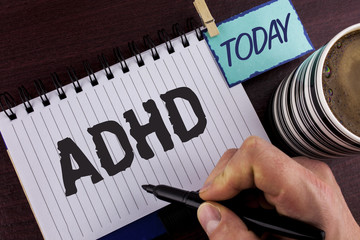 Handwriting text writing Adhd. Concept meaning Learning made easier for children teaching no more a difficult task written by Man on Notepad holding Marker in Hand wooden background Today Cup.