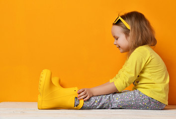 Young child baby  girl kid in yellow rubber boots sunglasses and t-shirt  sitting on yellow
