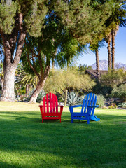 Red and Blue Adirondack Chairs in Shade of Pine