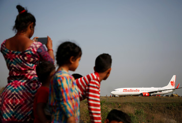 People look at an aircraft belonging to Malindo Air that skidded off the runway during take off last night at Tribhuvan International Airport in Kathmandu