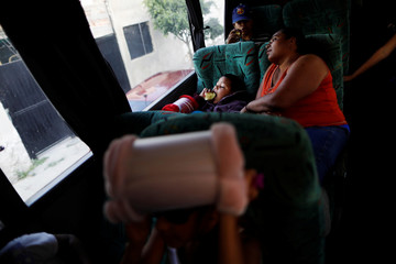 A Central American boy migrant, moving in a caravan through Mexico, eats an apple as he travels to Mazatlan as part of his new travel route, in Tlaquepaque