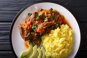 Ecuadorian seco de chivo stewed goat meat with a side dish of yellow rice and avocado close-up on a plate. horizontal top view