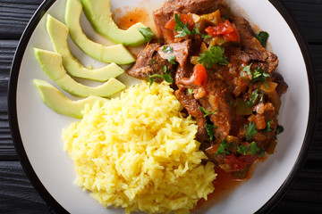 Seco de chivo is goat stew with yellow rice and avocado close-up on a plate. Horizontal top view