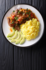 Portion of seco de chivo stewed goat meat with yellow rice and avocado close-up on a plate. Vertical top view