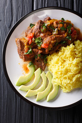 Ecuadorian seco de chivo stewed goat meat with a side dish of yellow rice and avocado close-up on a plate. Vertical top view