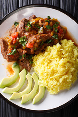 Seco de chivo is goat stew with yellow rice and avocado close-up on a plate. Vertical top view