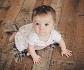 9 month old baby girl sitting on a wooden set on fur and looking at the camera.