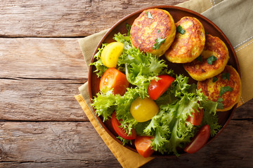 Freshly prepared potato pancakes are served with fresh salad close-up. Horizontal top view