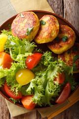 Ecuadorian potato pancakes llapingachos and fresh salad close-up on a plate. Vertical top view